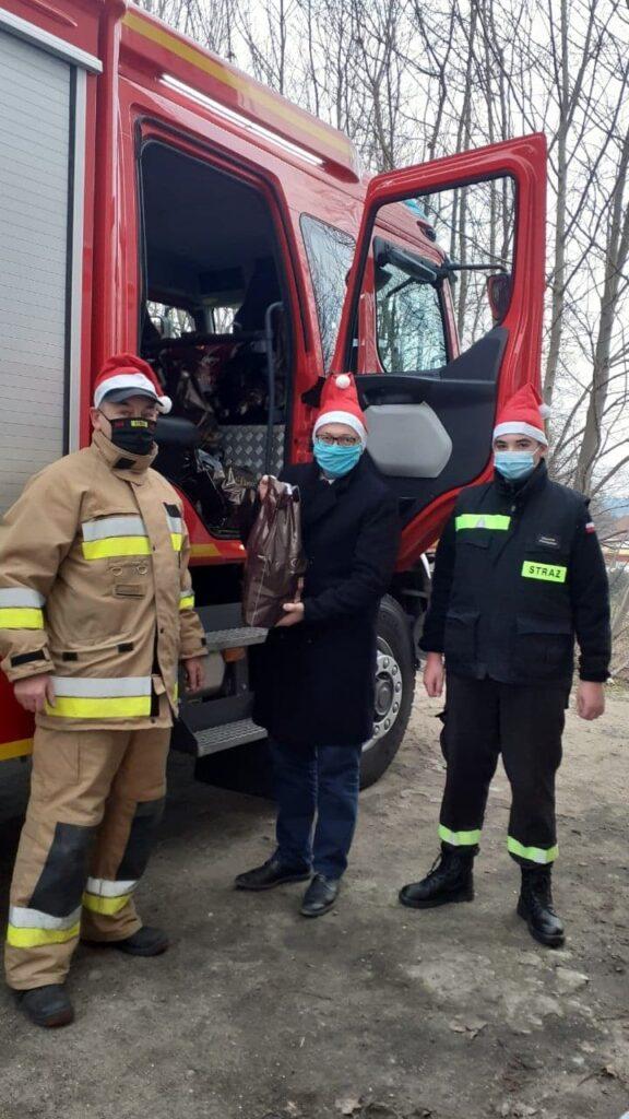 Zdjęcie strażaków przy wozie strażackim